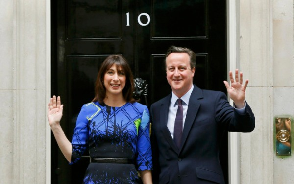 Britain's Prime Minister David Cameron and his wife Samantha wave as they return to Number 10 Downing Street after meeting with Queen Elizabeth at Buckingham Palace in London, Britain May 8, 2015. Prime Minister David Cameron won a stunning election victory in Britain, overturning poll predictions that the vote would be the closest in decades to sweep easily into office for another five years, with his Labour opponents in tatters.   REUTERS/Stefan Wermuth
